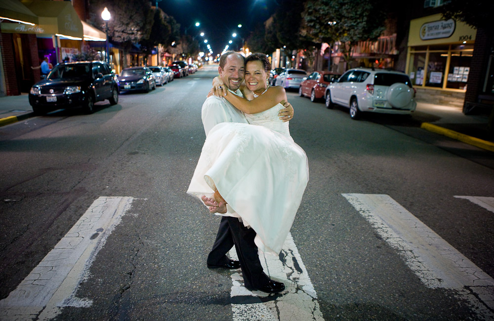 The wedding couple was all smiles as Matt carries his bride Michelle, in her bare feet, across the crosswalk on Main Street in Sumner, WA after their wedding and reception at The Attic. (Photography by Scott Eklund/Red Box Pictures)