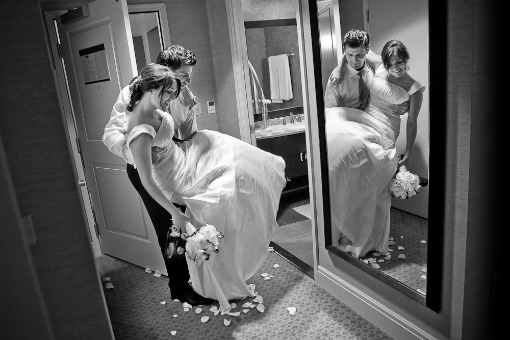 After a long day, Adrian carries Silvia over the threshold of their hotel suite following their wedding reception at the Hyatt Regency in Bellevue, WA. (Photo by Andy Rogers/Red Box Pictures)