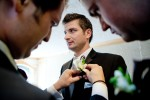 Adrian's groomsmen pin his corsage to his lapel as he waits for his first glimse of his soon-to-be bride Silvia at her Bothell, WA home. (Photo by Andy Rogers/Red Box Pictures)