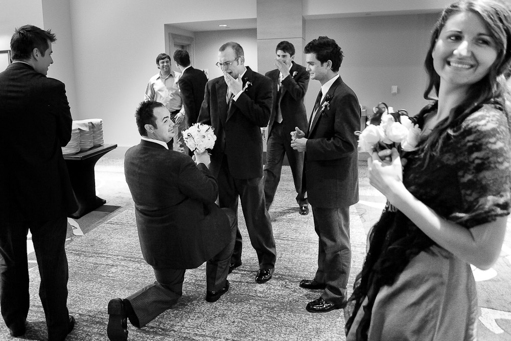 The best man pretends to propose to the bride's brother as the groomsmen joke round during the wedding reception at the Hyatt Regency in Bellevue, WA. (Photo by Andy Rogers/Red Box Pictures)