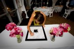 A wedding guest signs the mat board around a photograph of Scott and Pauline at their reception at the Golf Club at Newcastle near Seattle. Photography by Scott Eklund/Red Box Pictures)