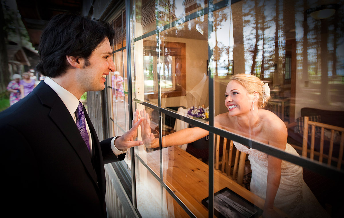 Nikko and Corrine touch through the window during their wedding at Kitsap Memorial State Park (Photography by Scott Eklund/Red Box Pictures)