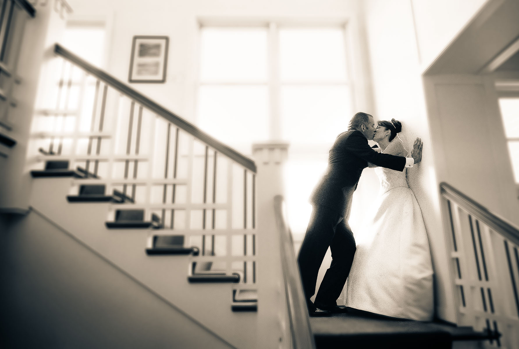 A bride and groom share a passionate kiss on the stairwell on their wedding day in Seattle. (Photo by Scott Eklund/Red Box Pictures)