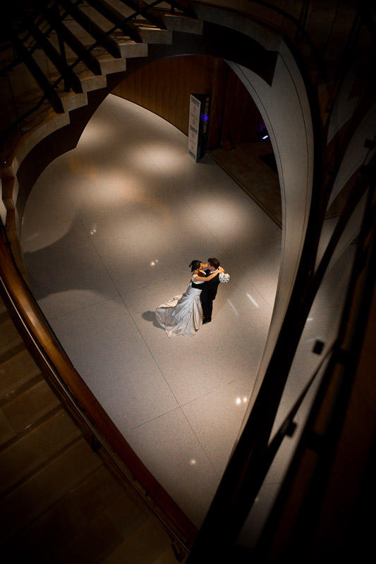 Silvia and Adrian embrace below the winding stairwells at the Hyatt Regency in Bellevue, WA following their wedding reception. (Photo by Scott Eklund/Red Box Pictures)