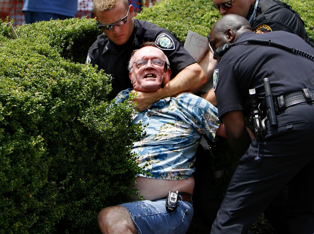 Ted Mitchell, 62, is arrested after refusing to relinquish the pole holding his American flag at an anti-illegal immigration rally in front of the Hamblen County Courthouse in Morristown, Tennessee. Fearing violence, about 100 state and local police officers were waiting at the square and outnumbered the participants of the rally.