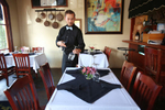 A server sets a table at Pinzone's Italian Downtown in Fairhope, Ala., on August 28, 2014.