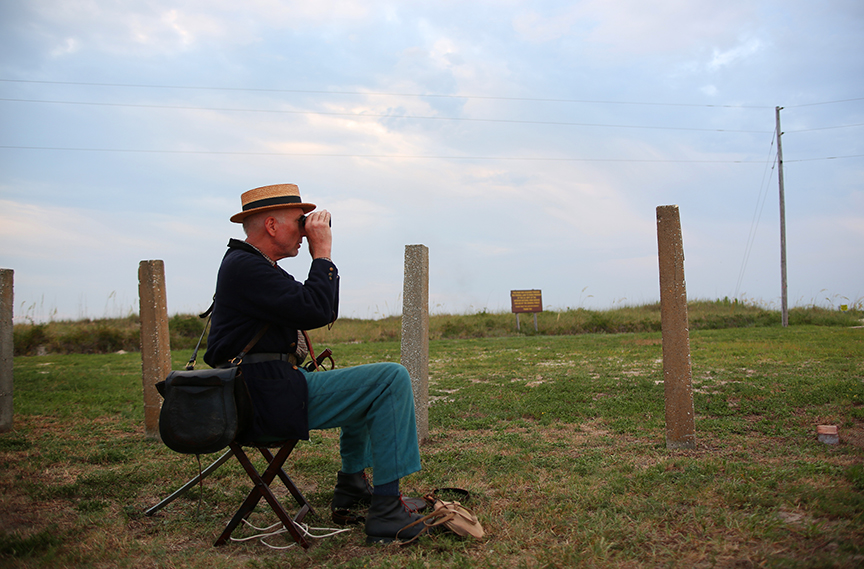 Mark Brainard of Chatanooga, Tenn., watches the artillery firing at the 150th Battle of Mobile Bay commemoration at Fort Morgan in Gulf Shores, Ala., on Friday August 1, 2014.