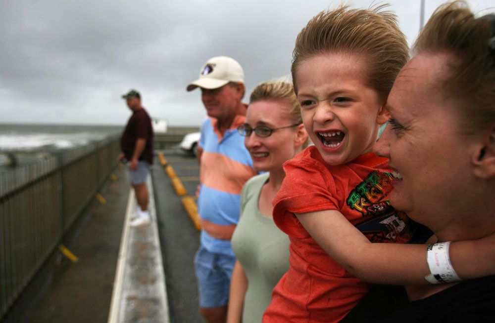 Wilson Hardin, 3, reacts to the strong wind as his grandmother Debra Hanes holds him as they watch surfers in Galveston brave the choppy surf brought on by Hurricane Humberto off the gulf coast.