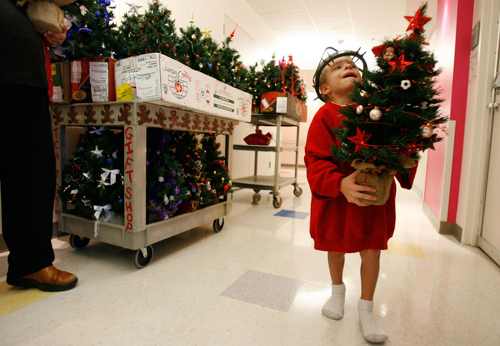 A patient at Texas Children's Hospital in Houston, Texas carries his decorated Christmas tree to his room. Over 100 trees were donated by a local florist.