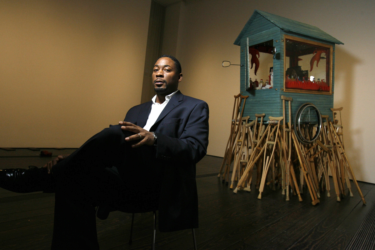 Franklin Sirmans, the Menil Collection's curator of modern and contemporary art, poses near a piece included in the exhibition {quote}NeoHooDoo: Art for a Forgotten Faith{quote} on June 12, 2008 in Houston.