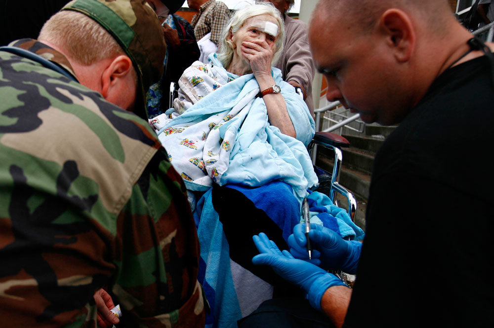 Alina Van Epps, who is wheelchair bound, is evaluated by rescue personnel at Ball High School as she waits to be evacuated on Galveston Island on Sunday, Sept. 14, 2008, in Galveston after Hurricane Ike. She rode out the storm in her flooded home and suffered a blow to her head.