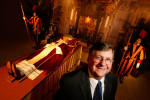 Vice Chairman/President of the National Museum of Funeral History, Bob Boetticher, poses near an exhibit of a pope lying in repose inside St. Peter's Basilica with Swiss Guards at the museum in Houston. The National Museum of Funeral History is the only permanent exhibit of Papal artifacts outside of the Vatican.