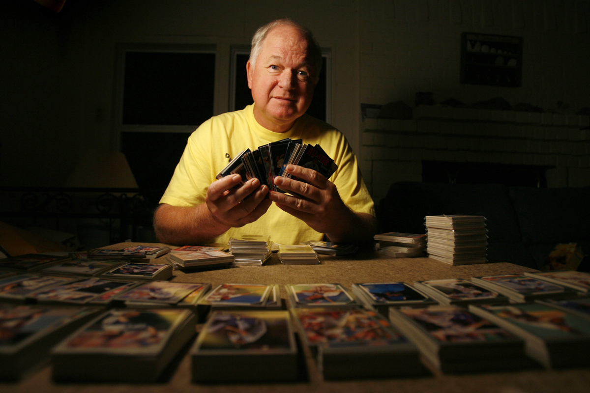 Duffy Burnett poses with some of his sports cards at his sorting table in his home on December 12, 2008 in Kingwood, TX. He and his wife donate hundreds of thousands of sports cards to local charities each year.