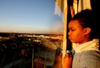 Brittany Powell, 13, looks out her hotel window in late December 2005 at the Windsor Suites Hotel in Houston. She and her family were Katrina evacuees who had been living in hotels for 4 months. She and her 5 siblings and cousins had been out of school since the hurricane.