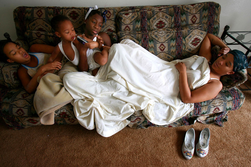 From left, Brittany Powell, 13, Myron Powell, 2,  Deiondrea Powell, 13, and Shawn Powell relaxed in their Houston apartment on a sofa given to them by relatives in January 2006. They were  waiting for FEMA furniture which never arrived.