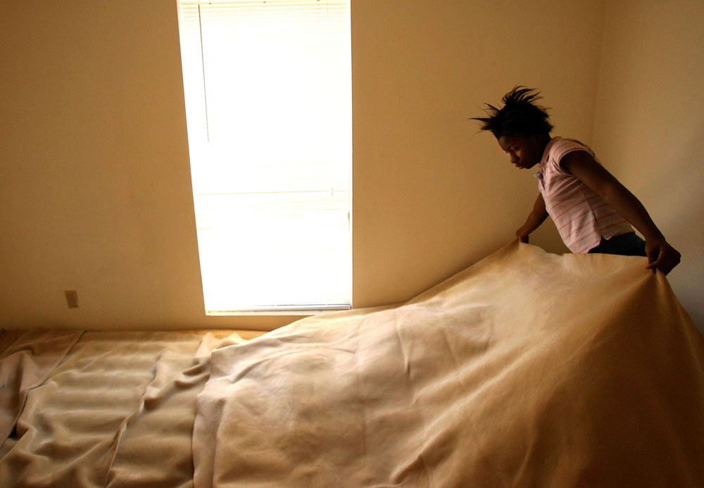 Deiondrea Powell, 13, straightens up her air mattress bed in Houston in February 2006 while at home babysitting her two-year-old cousin Myron instead of going to school. Shawn left the boy with Deiondrea as she gathered documents required to enroll her two younger daughters in elementary school in Houston.