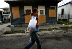 Shawn Powell carries groceries home in late April 2006 in the New Orleans seventh ward neighborhood she lived in for two months with her three daughters, two nieces and young nephew. The family, who was caught in the floodwaters of Hurricane Katrina in their 8th ward neighborhood in August 2005, found that the city was unlivable eight months later. Their duplex, which had been flooded, lacked a gas connection for hot water and debris and garbage littered the neighborhood.