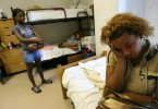 Shawn Powell, right, sits in the room she is sharing with her three daughters, two nieces and young nephew ranging from 2-years-old to 14 in June 2006 at the Salvation Army homeless shelter in Austin where she had been living for several weeks since finding herself homeless after a failed attempt to return to New Orleans.