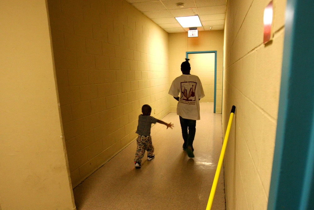 Myron Powell, 2, and his cousin Deiondrea, 13, walk in the corridor of the family dorm in June 2006 at the Salvation Army homeless shelter in Austin where they lived for several weeks after becoming homeless with their aunt Shawn Powell after a failed attempt to return to New Orleans.