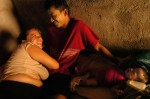 Lesly Montoya, 30, and her boyfriend of four years, Wilson Rene Martinez Ramos, 22, share a light moment as their two-month-old son Wilson Estuardo Martinez Montoya fusses in their San Pedro Sula, Honduras home.