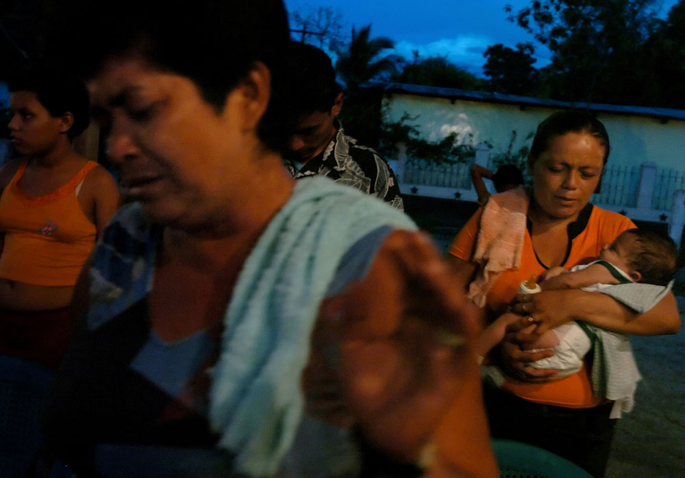 Lesly Montoya attends an evangelical church service in the neighborhood of her older sister, Reina Grande, 42, front, in San Pedro Sula, Honduras. Lesly and her boyfriend Wilson Martinez brought their two-month-old son Wilson to be blessed by the minister. Reina is the only family member Lesly has told about her HIV status.
