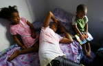 From left, Brishawn Powell, 7, her sister Brittany Powell, 13, and their cousin Myron Powell, 2, rest in their New Orleans seventh ward duplex.