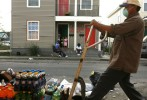 A worker deposits spoiled food and drinks on the street where Shawn Powell and her family were living for two months in the seventh ward neighborhood of New Orleans. The food had been rotting for seven months in the liquor store across the street.
