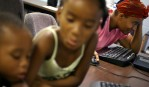 Shawn Powell passes the time in June 2006 checking her e-mail and looking for employment in the computer lab of the Salvation Army in Austin while her daughter Brishawn Powell, 8, and nephew Myron Powell, 2, play next to her. Shawn had grown increasingly frustrated and depressed as she reached the two month mark in the shelter with her three children and three nieces and nephews.