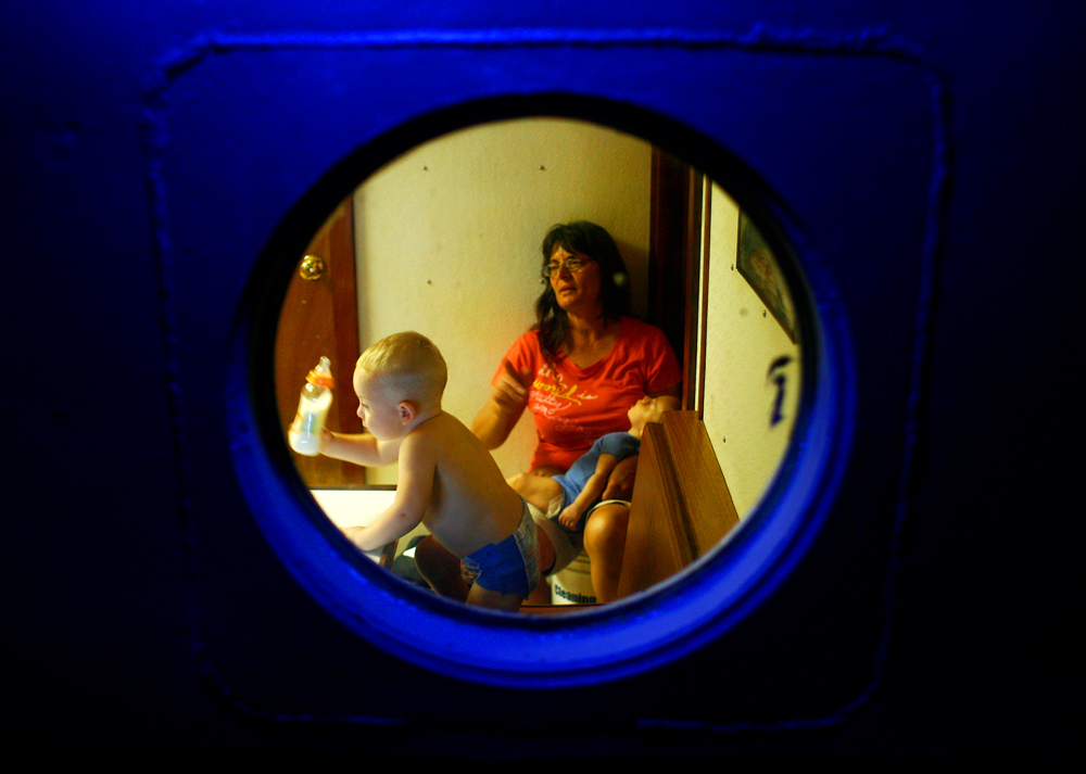 Seen through a porthole, Margaret Shiver watches television and babysits her grandson Kaleb Shiver, 2, in the tug boat