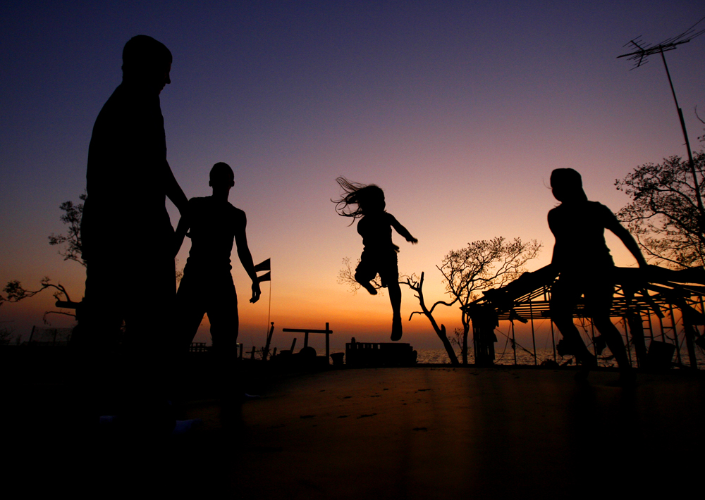 Children play on a trampoline at dusk on Oak Island.
