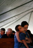 Jami Chavez prays with her son Samuel Chavez, 7, during Sunday services outside at Oak Island Baptist Church on Sunday, Sept. 28, 2008, in Oak Island.  The church held Sunday services outside for the second week in a row after Hurricane Ike destroyed most of the homes and buildings in the community. The Chavez family lost their home and is staying in a home with five other displaced families.