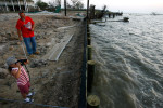 Michael Casonover and his girlfriend's daughter Zoe Key, 6, look out over the bay near the site where they lost their home during Hurricane Ike.