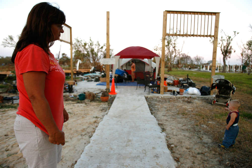 Margaret watches her grandson Kaleb Shiver, 2, near the slab where her home once stood on Saturday, Oct. 4, 2008, in Oak Island.
