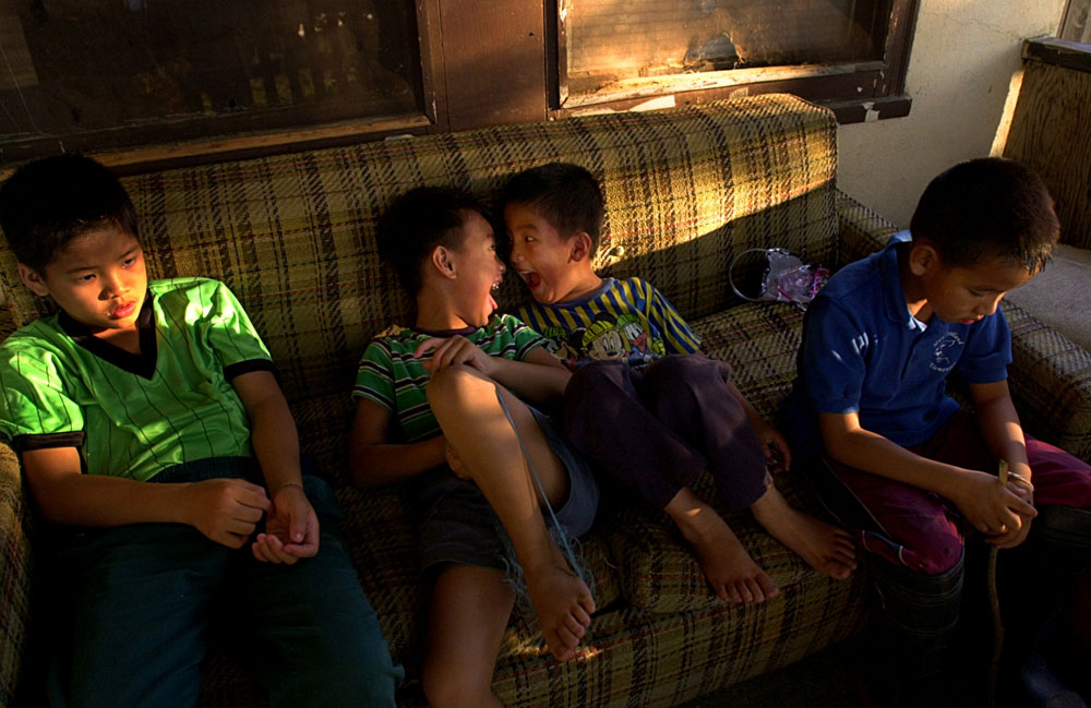 Phillip Bee, 5, center left, makes funny faces with Jerry Xiong, 6, as they relax with their family on their front porch in Marysville, CA. The porch provided a shady spot for the boys to enjoy the late afternoon as temperatures reached 94 degrees.