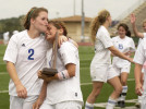 Friendswood High School's Kristen Bowen, left, and Casey Regian right, carry their team's trophy as they celebrate their victory against Midway High School of Waco in the Girls 4A Region III Championship Tournament at George Turner Stadium on Saturday, April 4, 2009, in Humble. Friendswood won 2-0.