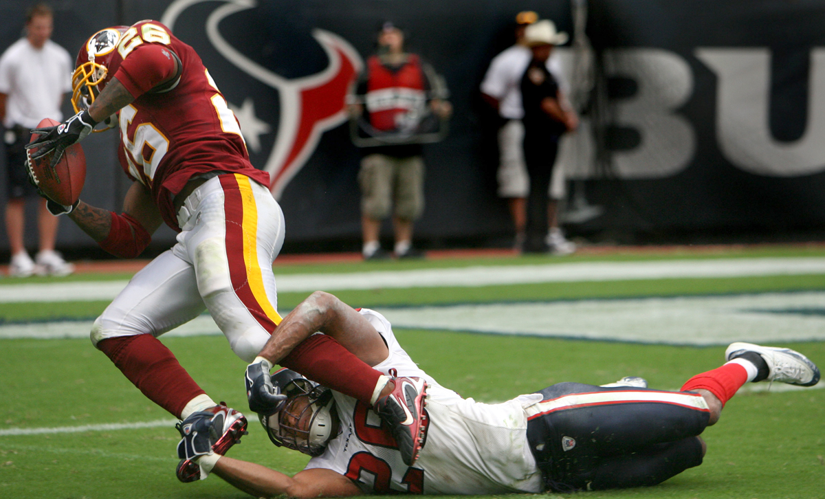 Redskins Clinton Portis runs the ball against interference from Texans Glenn Earl, right, in the third quarter of Sunday's game at Reliant Stadium Sunday September 24, 2006. The Redskins won 31-15.