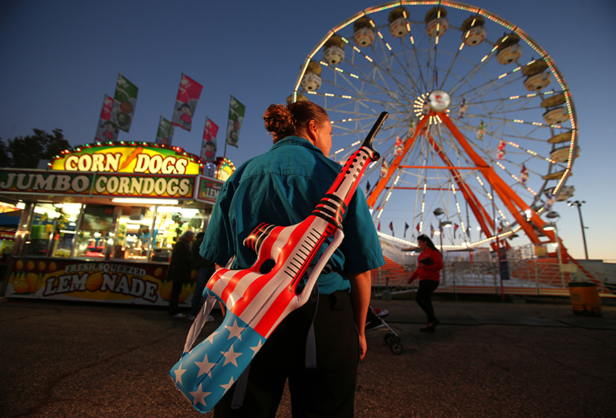 A game attendant displays one of her prizes as she waits for the next player at the Greater Gulf State Fair in Mobile, AL on Oct. 25, 2013.