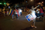 A Chavez supporter cheers at passing motorists as thousands celebrated in downtown Caracas on Sunday night.