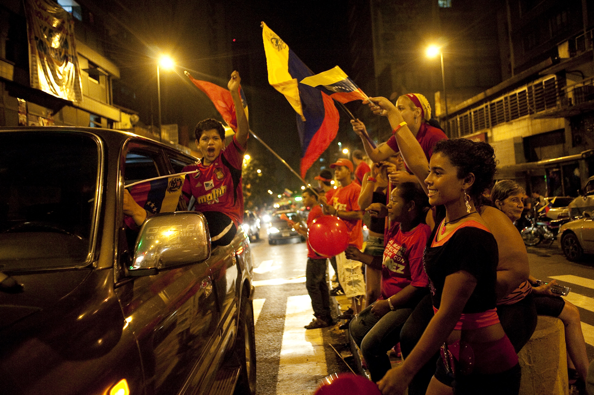 Chavez supporters cheer at passing motorists as they  celebrate in downtown Caracas.