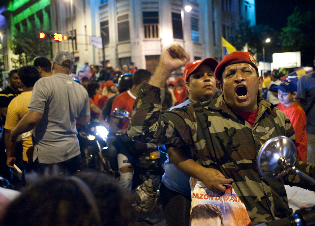 A Chavez supporter cheers from his motorcycle in downtown Caracas as he celebrates the president's re-election.