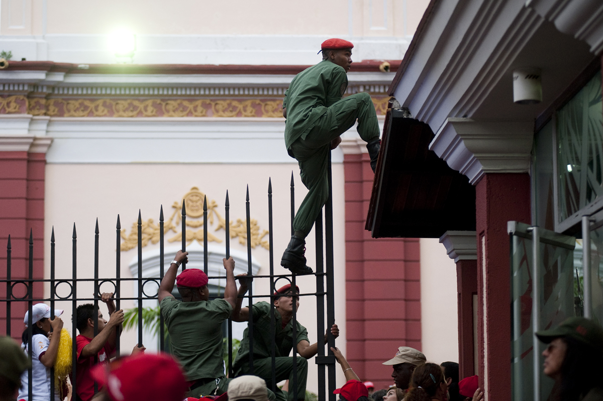 A soldier responds to a security threat outside Miraflores, the presidential palace, on Friday, April 13, 2012, in Caracasduring a celebration on the anniversary of Chavez's return to the presidency on April 13, 2002 after a failed coup.