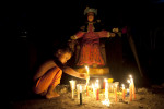 A child lights candles at an altar to Niño de Atocha, the patron saint of those unjustly imprisoned, a protector of travelers, and rescuer of those in peril during the annual celebration of Venezuela's María Lionza religious cult at Sorte Mountain in the state of Yaracuy, Venezuela.