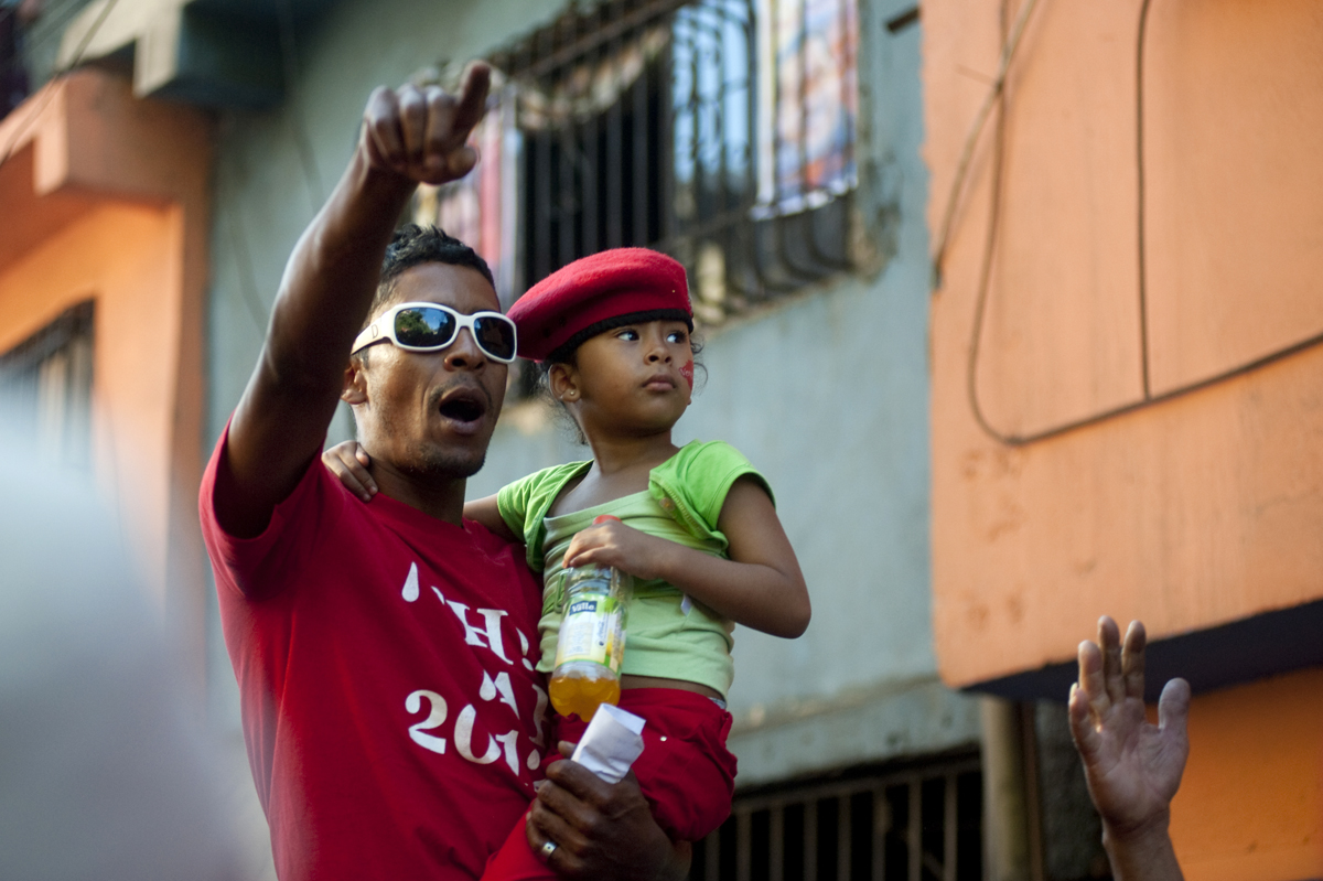 Supporters of President Hugo Chavez cheer as they see him arriving in the Petare neighborhood of Caracas, Venezuela as he continues his re-election campaign on his 58th birthday on Saturday, July 28, 2012.