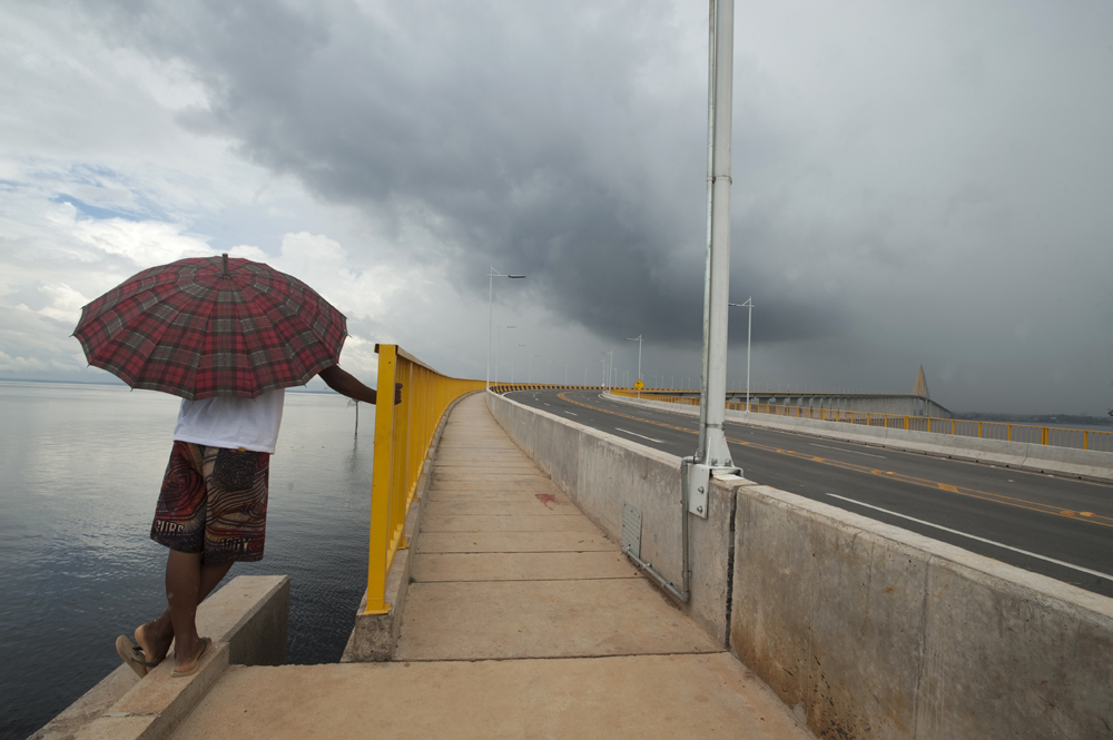 A local man gazes out at the Rio Negro branch of the Amazon River from the end of the Manaus-Iranduba Bridge deep in the Brazilian Amazon. This 3.5 km long bridge was completed last year and is the first to cross the world's greatest river system. It connects three undeveloped towns to Manaus, Brazil. The bridge brings economic opportunities for those living on the far bank but environmentalists fear it because it could open up the fragile rainforest surrounding Manaus to further destruction. But, the locals on the undeveloped side are elated. They can now drive to the city in minutes. In the past, ferrying a vehicle across was too expensive for most at fares as high as $50.