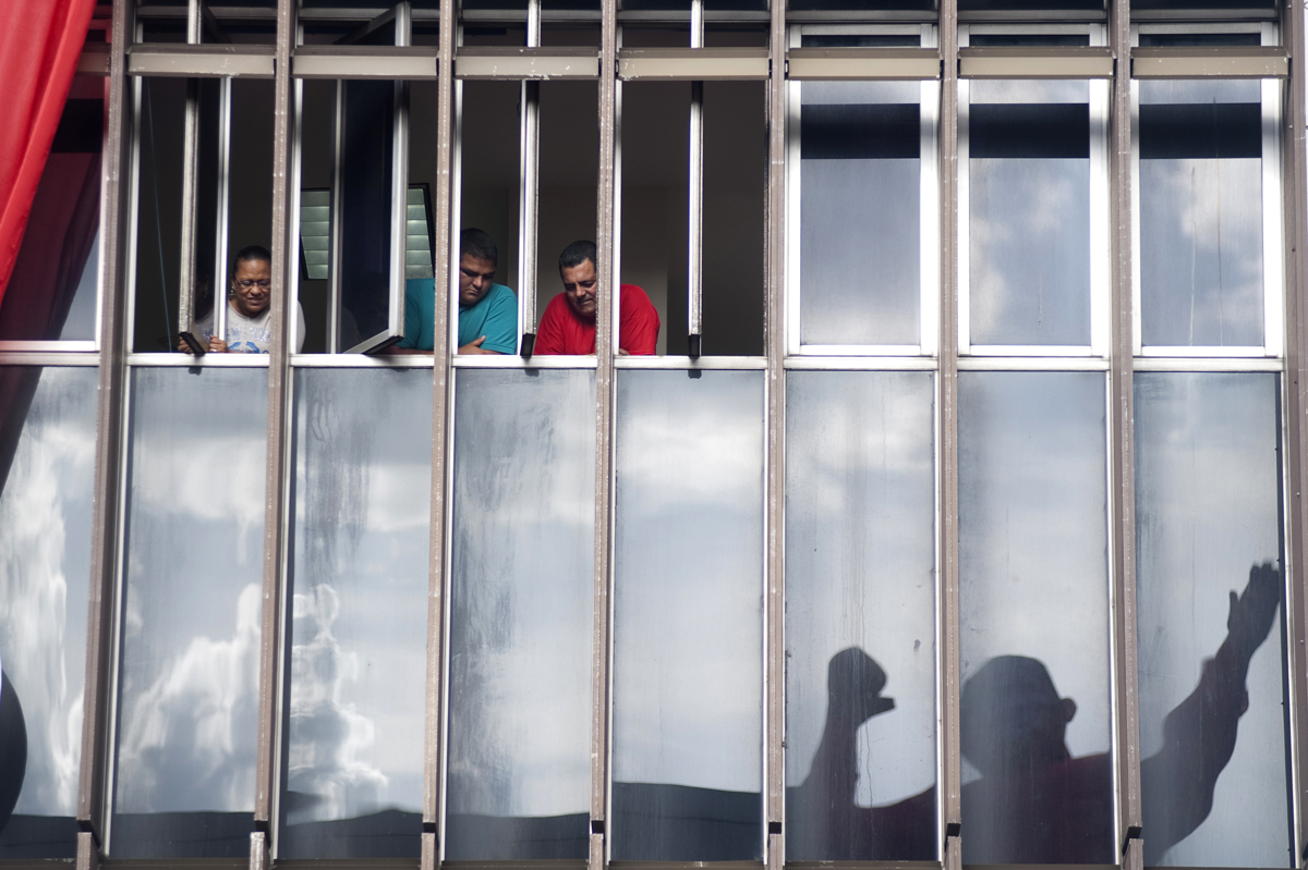 Office workers watch a rally for Hugo Chavez in downtown Carcas on Monday, June 11, 2012.