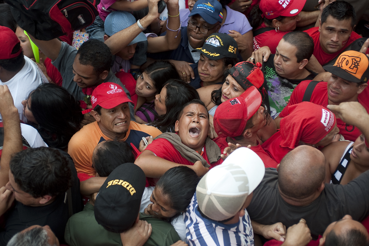 A young boy screams as he is trapped in a mob during a rally for Hugo Chavez in Caracas, Venezuela on Monday, June 11, 2012.