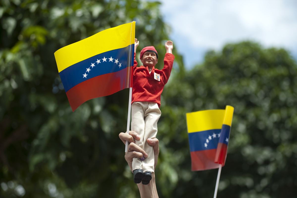 A Chavez supporter holds up a Chavez doll as he waits for Chavez's arrival at a voting center on election day in the 23 de Enero neighborhood of Caracas.