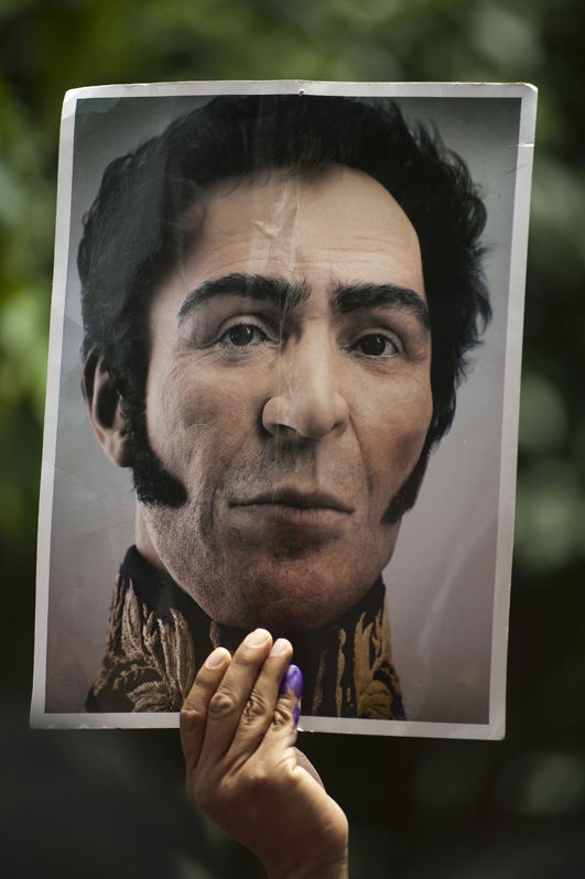 A man with his finger dyed after voting holds up a poster of Simon Bolivar, a Venezuelan military leader who was instrumental in the revolutions against the Spanish empire in Latin America.