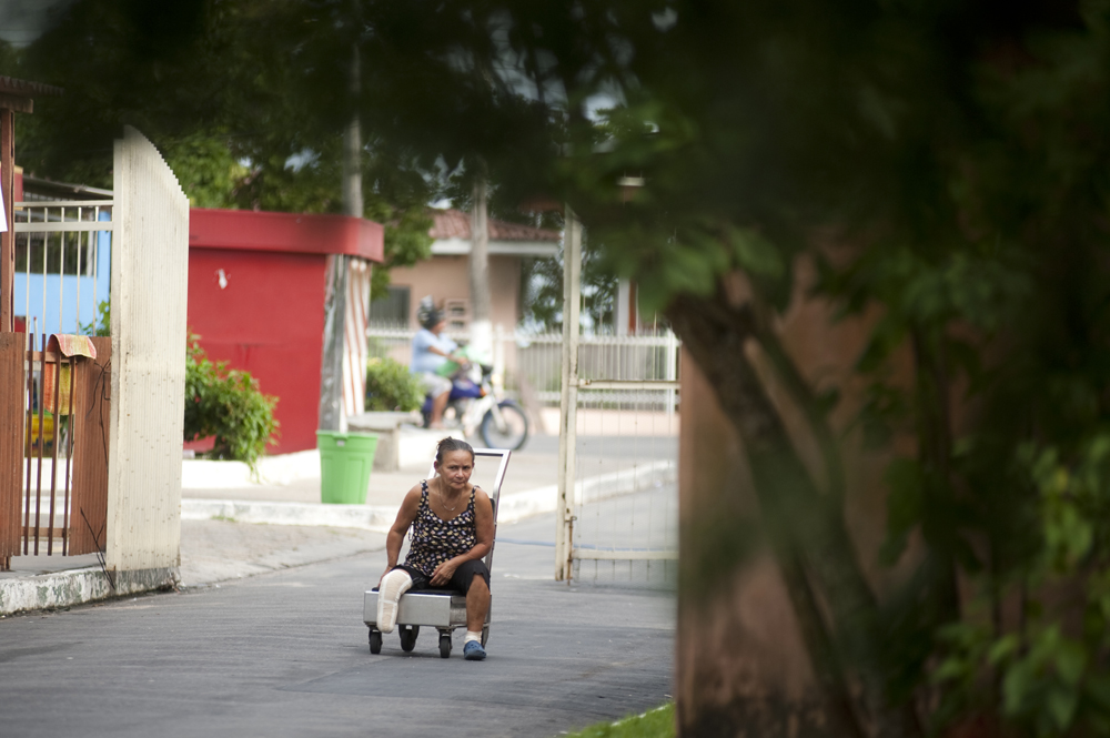 Ira Cema de Souza, 53, moves herself along the main road into the Colonia Antonio Aleixo leprosarium on Monday, March 12, 2012 in Manaus. She came to the leprosarium for treatment from a remote location four days up the Amazon River.