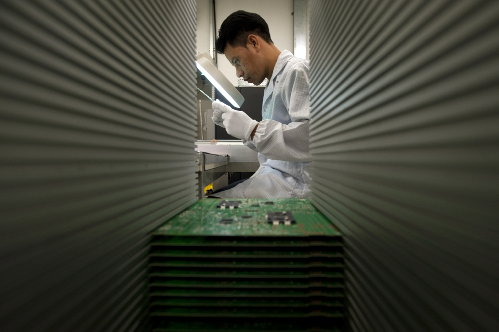 Elman Fernandez, 30, inspects a motherboard inside the Technicolor factory in Manaus, Brazil.  Hundreds of manufacturers are located in the Amazonian city where the government has provided tax breaks that encourage industrial development in the area. The free trade zone has created urban jobs for workers who might otherwise have been putting further strain on the surrounding rainforest with logging or illegal farms. Photographed on Wednesday, March 14, 2012, in Manaus.